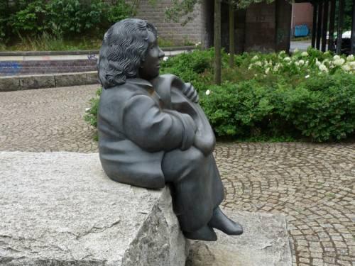 Skulptur eines sitzenden Mädchens, das ein übergroßes Ohr in den Händen hält