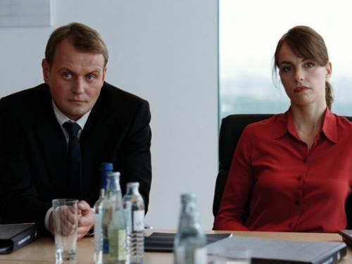 Mann und Frau an einem Schreibtisch mit Akten und Wassergläsern.