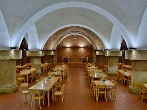 Raum mit Tischen und Stühlen unter einem gewölbten Dach.