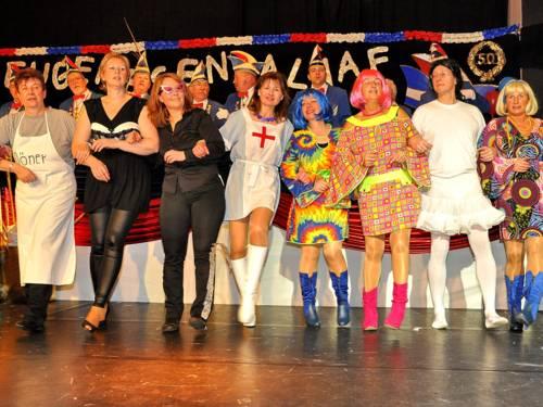 Verschieden verkleidete Frauen tanzen in einer Reihe auf einer Bühne.