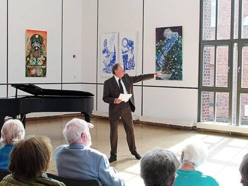 Mann steht in einem Raum vor sitzendem Publikum und zeigt auf Bilder.