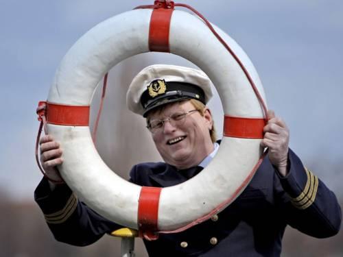 Kapitän mit Rettungsring vor dem Gesicht