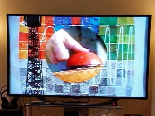 Fernsehbild in Farbe, das einen einen Daumen, der auf einen Knopf drückt, zeigt