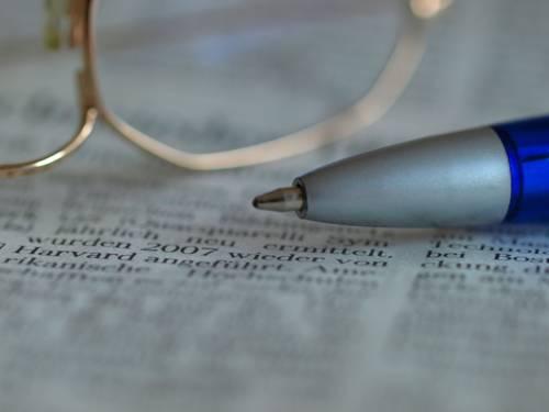 Zeitung, auf der ein Kugelschreiber und eine Brille liegen.