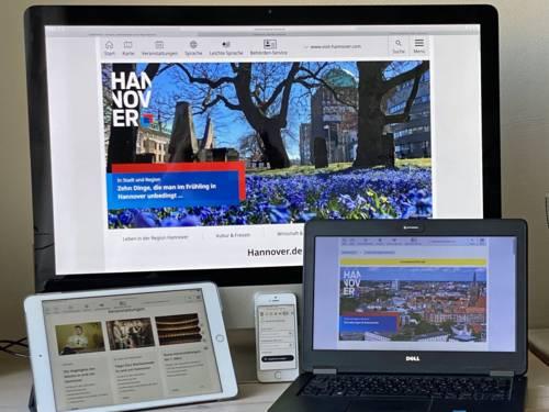 Es sind mehrere technische Geräte zu sehen: Ein Desktop-Computer, ein Smartphone, ein Handy und ein Laptop
