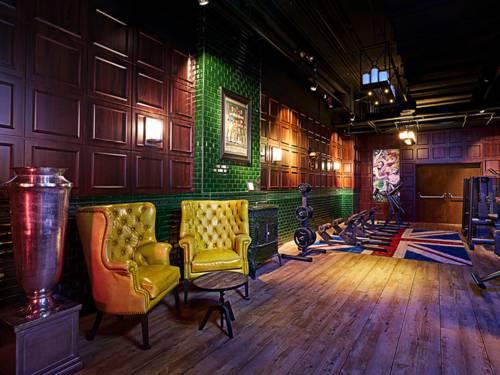 Edle Sessel, Holzvertäfelungen und Fitnessgeräte auf Teppichen.