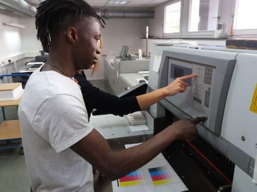 Zwei Menschen bedienen gemeinsam einen großen Drucker.