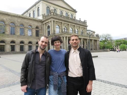 Eine Frau und zwei Männer stehen vor dem Operngebäude.