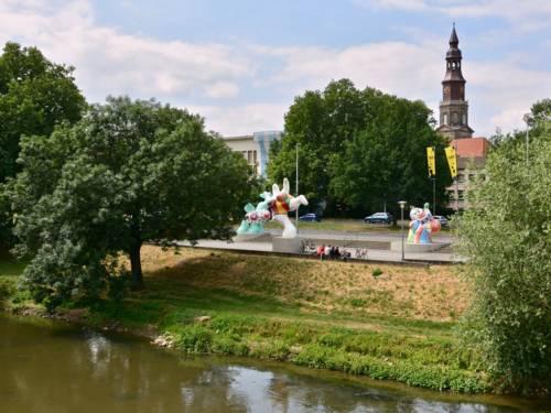 Blick über einen kleinen Fluss an dessen anderem Ufer Kunststatuen stehen.