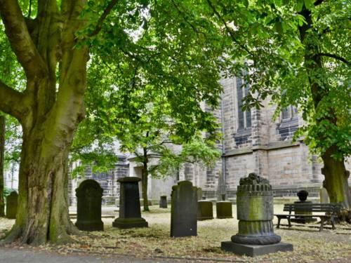 Vor einer Kirche stehen Grabsteine, Bäume und Bänke.