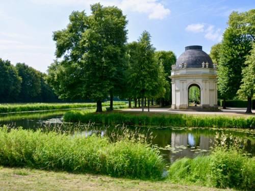 An einer künstlich angelegten Graft steht ein runder Tempel.