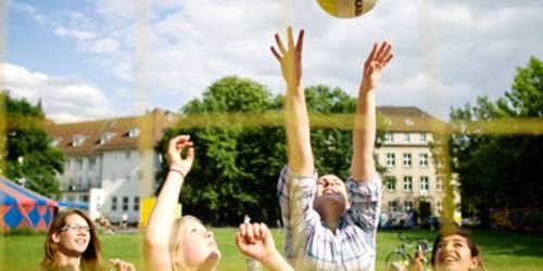 Jugendliche spielen Beachvolleyball.