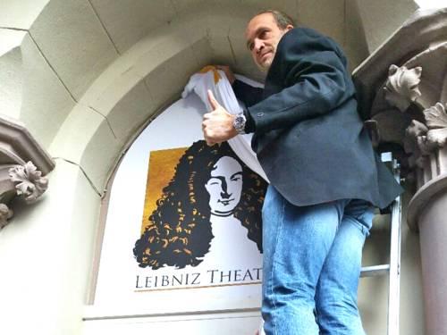 Ein Mann auf einer Leiter enthüllt in einem steinernen Portal das Bild eines zwinkernden Leibniz.