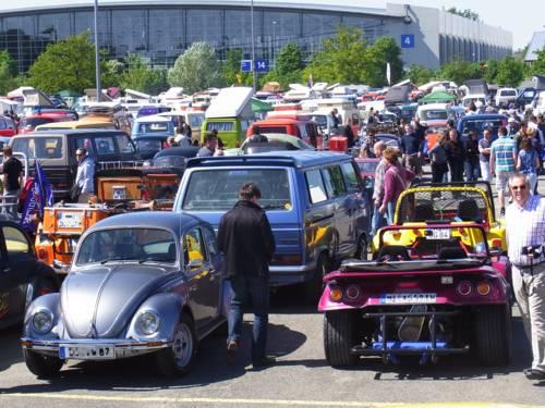 Viele Fahrzeuge auf einem Parkplatz, den Autokennzeichen nach aus vielen verschiedenen Städten.