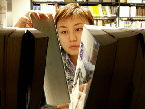 Ein junge Frau schaut sich Bücher in einem Regal an.