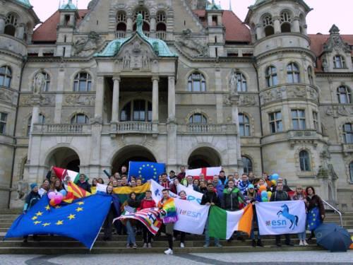 Menschen mit Flaggen vor einem Gebäude