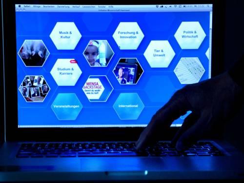 Aufgeklappter Laptop-Computer mit Hand.
