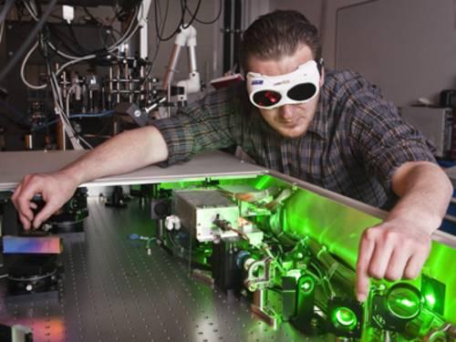 Ein Mann mit Schutzbrille führt ein physikalisches Experiment durch.