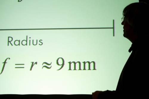 Ein Mann schaut auf eine Wand mit Formeln.