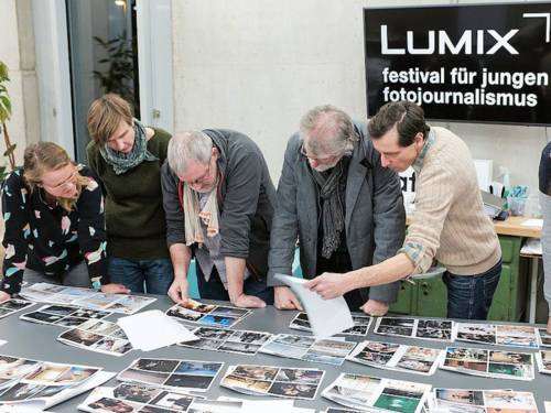 Fünf Menschen beugen sich über einen Tisch mit Fotos.