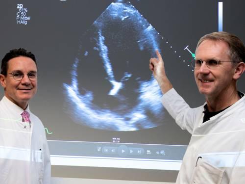 Zwei Männer in weißen Kitteln vor einem Bildschirm mit Ultraschallaufnahme.