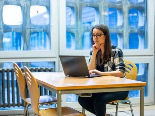 Frau an einem Tisch sitzend mit Notebook
