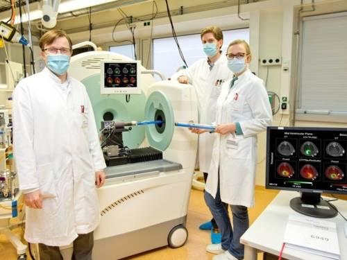 Zwei Männer und eine Frau in weißen Kitteln mit Mund-Nasenschutz-Masken vor einem großen medizinischen Gerät.