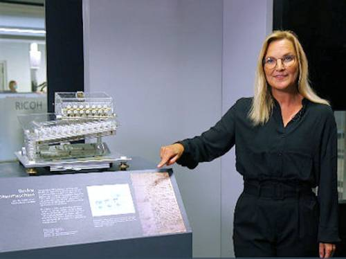 Frau zeigt auf ein Exponat in einer Ausstellung