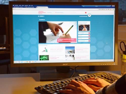 Computerbildschirm, im Vordergrund Hände auf einer Tastatur.