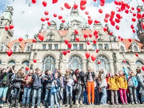 Viele Kinder stehen vor einem alten Gebäude und lassen rote Luftballons fliegen.