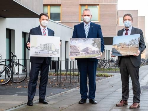 Drei Männer mit Nasen-Mundschutz-Masken halten Bilder in den Händen