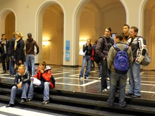 Mehrere Studenten stehen auf einer Treppe in einem Gebäude.