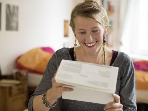 Lächelnde junge Frau mit Zettel in den Händen.