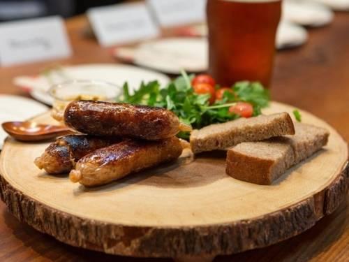 Holzbrett mit Würstchen, Salat und Brot