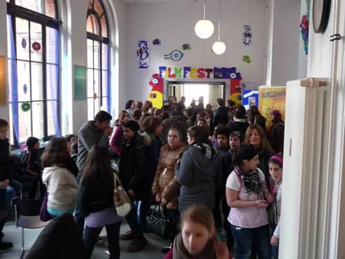 Ein Kino-Foyer mit vielen Kindern und Erwachsenen.