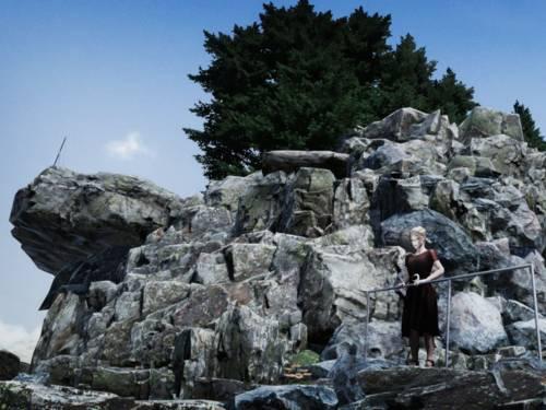 Frau auf einem Aussichtspunkt an einem Felsen