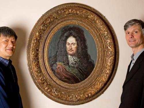 Zwei Männer neben einem historischen Porträt