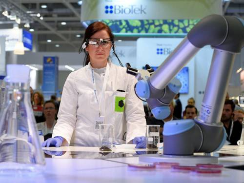 Frau in weißem Kittel mit Schutzbrille und Industrieroboter