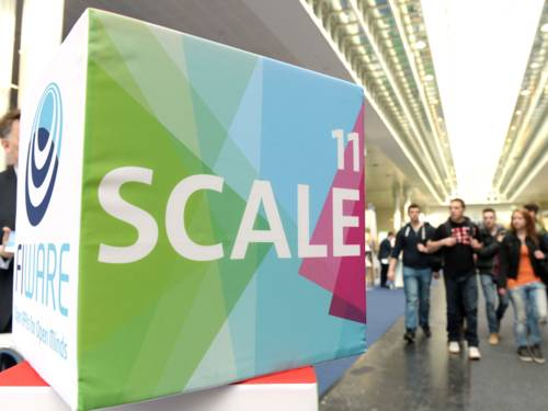 The logo SCALE11 on a block, several young people in the background.