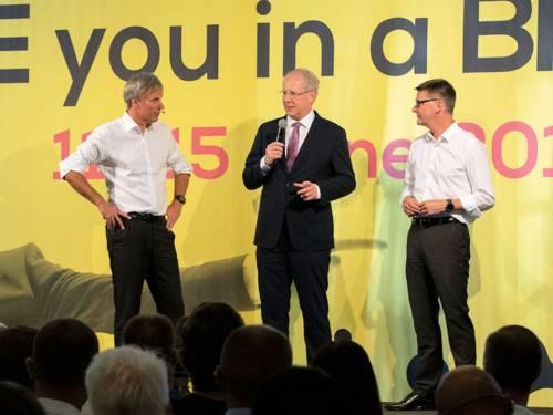 Drei Männer stehen auf einer Bühne