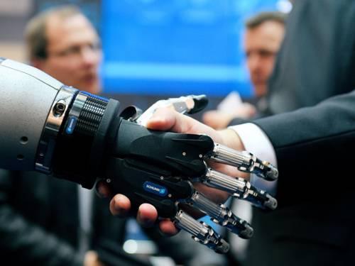 Handschlag zwischen einer menschlichen und einer Roboterhand.