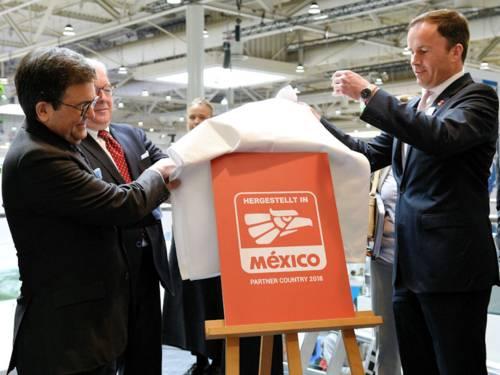 """Zwei Männer enthüllen eine Tafel mit der Aufschrift """"Mexiko"""""""