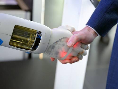 Händeschütteln einer menschlichen Hand mit einer Roboterhand