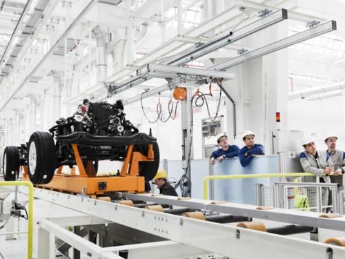 Ein Motorblock auf einem Produktionstransportband, rechts sind vier Arbeiter zu sehen