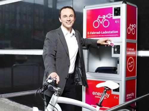 Mann mit Fahrrad vor E-Fahrrad-Ladestation