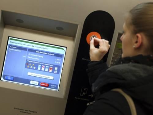Frau steckt Münze in einen Fahrkartenautomaten