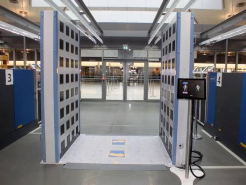 Zwei Metallplatten in ca. einem Meter Abstand. Dazwischen sind auf dem Fußboden zwei Fußmarkierungen angebracht. Ein kleiner Monitor davor zeigt zwei schematisierte Abbildungen menschlicher Körper.