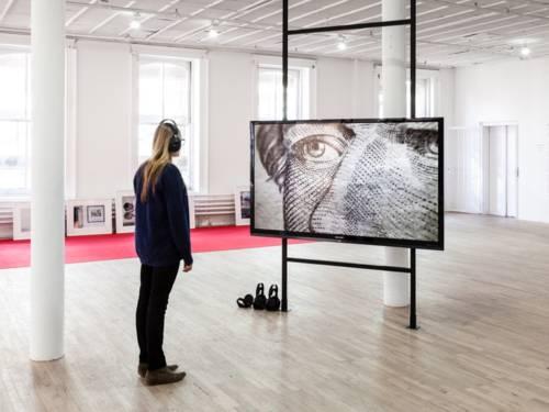 Mann steht in einem Raum vor einem an ein Regal moniterten Großflachbildschirm, auf dem die Grafik eines ihn anblickenden Gesichts zu sehen ist.