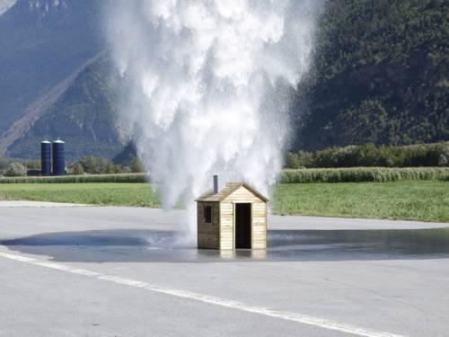 Haus auf einer Straße, auf das Wasser stürzt
