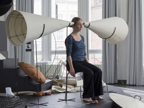 Frau sitzt zwischen zwei großen Klangtrichtern aus Papier